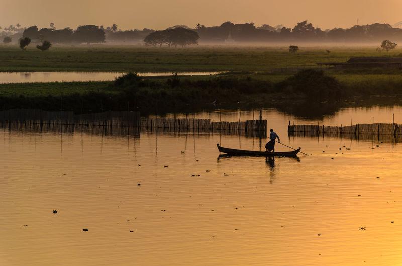 Man sailing boat on lake at sunset