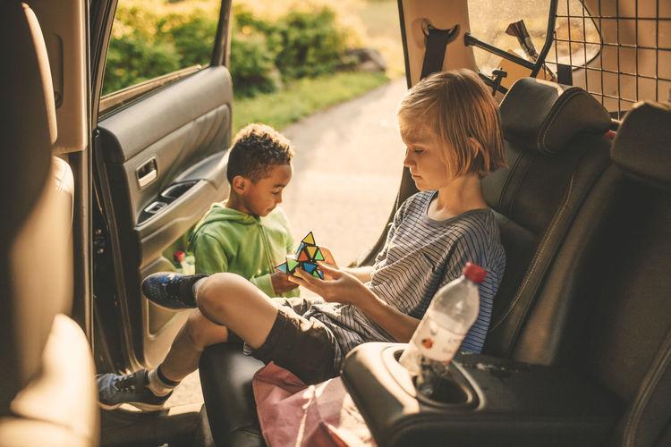 Rear view of boys sitting in car