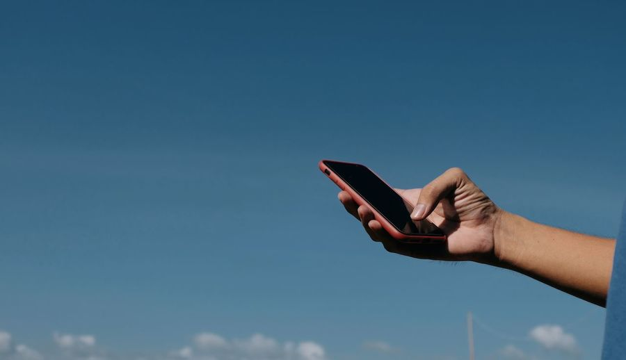 Midsection of person holding mobile phone against blue sky