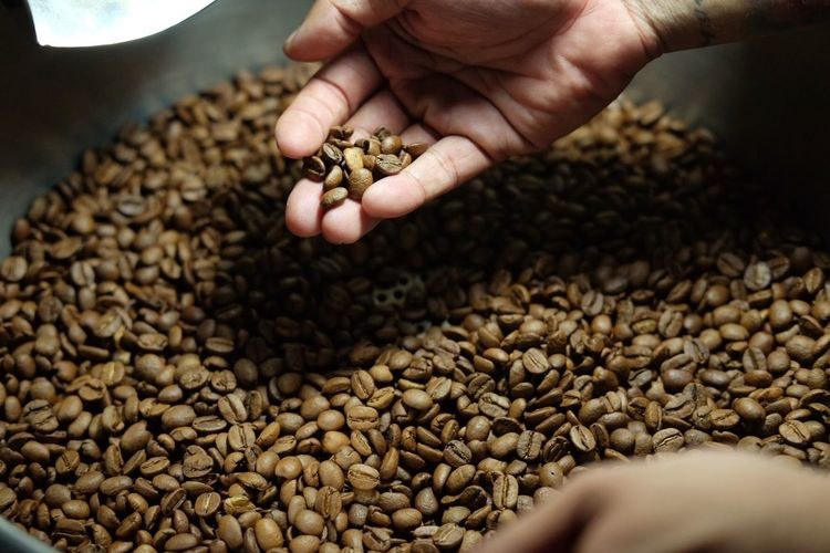 Cropped hand of person holding roasted coffee beans