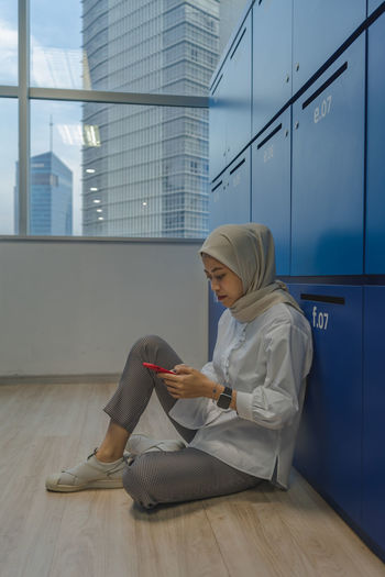 Side view of woman sitting on wooden floor