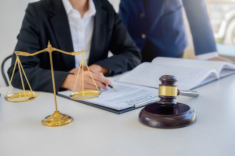 Midsection Of Lawyer With Colleague Working In Office
