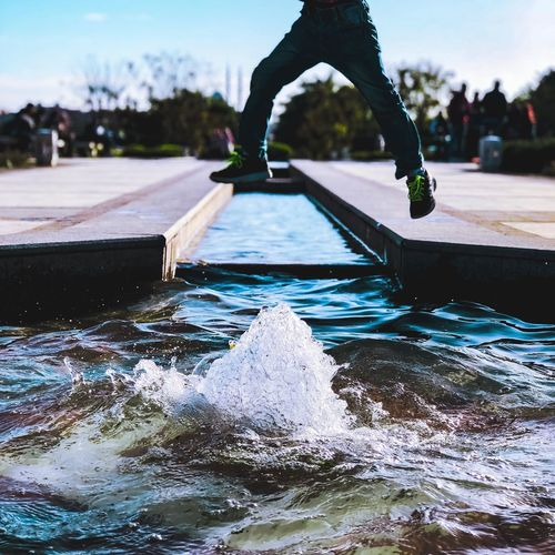 Low Section Of Man Jumping Over Fountain