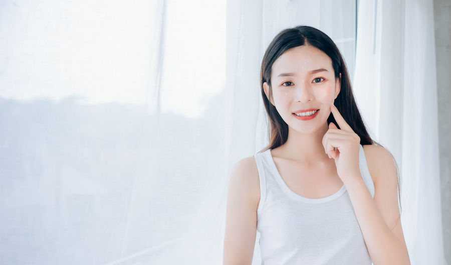 Portrait of Young Beautiful Asian woman clear face skincare her happy and smile at white room,Copy space. Portrait Young Adult Looking At Camera One Person Front View Indoors  Beautiful Woman Adult Waist Up Young Women Women Lifestyles Casual Clothing Happiness Tank Top Smiling Beauty Hair Hairstyle