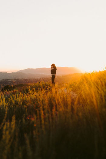 Side view of person standing on grassy field against sky during sunset