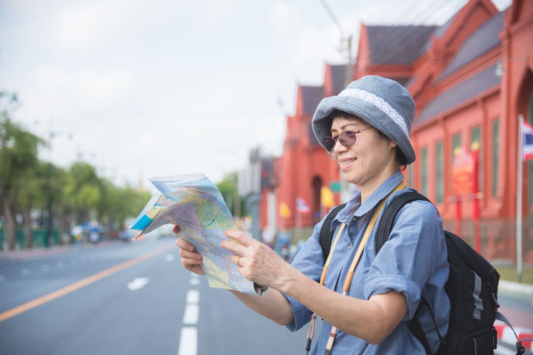 Senior Woman Travel Old Tourist Map City Traveling Tourism Lifestyle Happy Female Mature Single Walking People person Journey Vacation Smiling Outdoors One Trip Town Traveler Street Hat Backpack Reading Elderly Activity Retirement Retired Visiting Visitor Traveller Backpackers Lady Urban Summer Asian  Thailand Chinese Korean Taiwanese