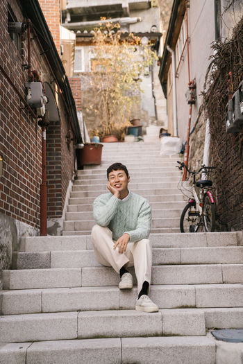 Portrait of young man sitting on staircase in city