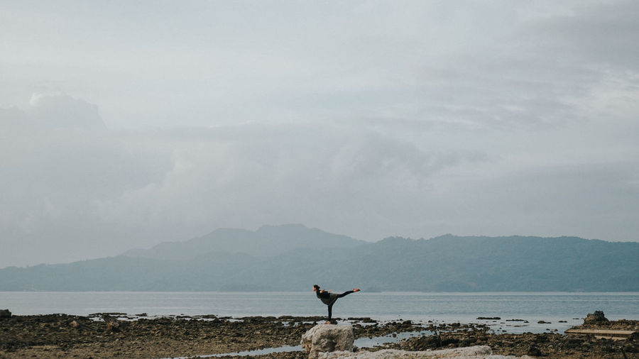Man doing yoga on rock by sea against sky