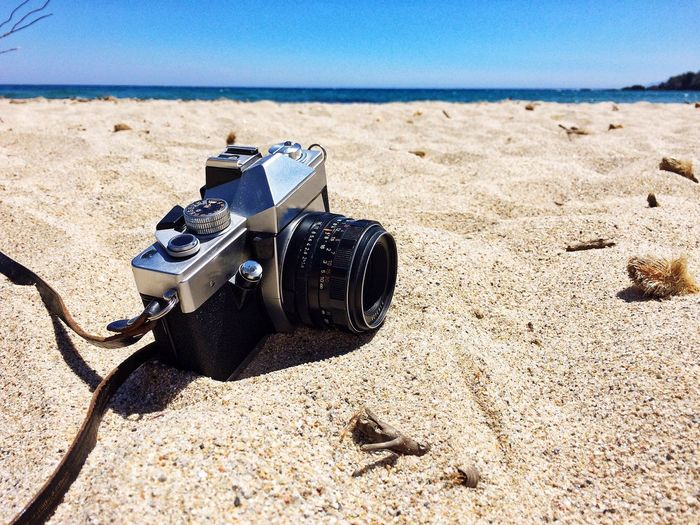 Close-up of camera on sand at beach against sky