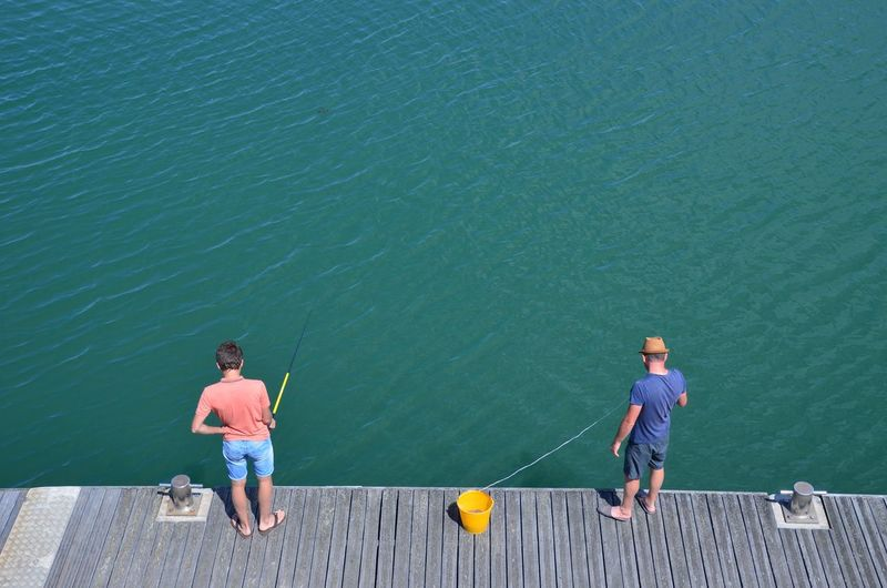 High angle view of men fishing while standing on pier at lake