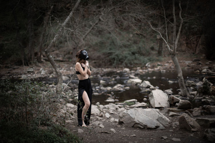 Side view of woman wearing gas mask while covering chest in forest