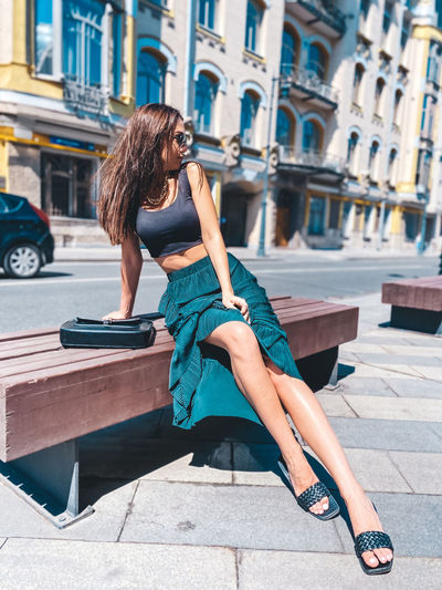 Full length of woman sitting in city