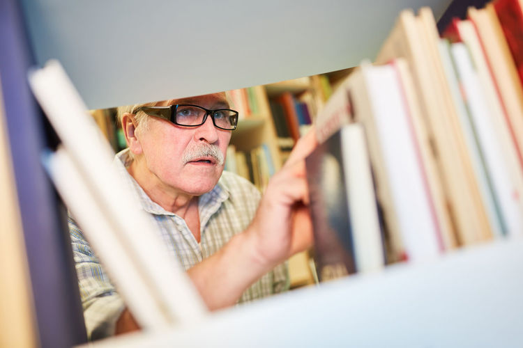 Senior man searching book at bookshelf in library