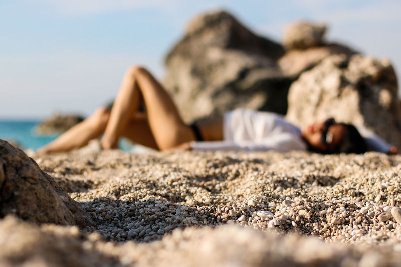 Low Section Of Woman Lying On Rock At Beach