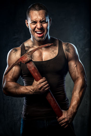 Aggressive Muscular Man Holding Pick Axe Against Wall