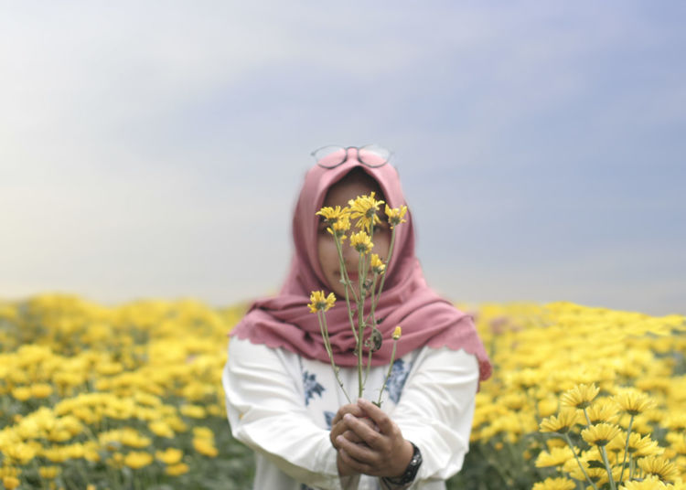 Midsection of person holding yellow flower in field