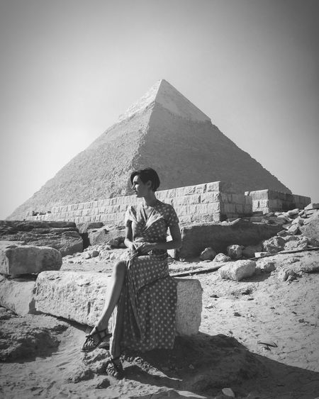 Full length of young woman sitting against pyramid