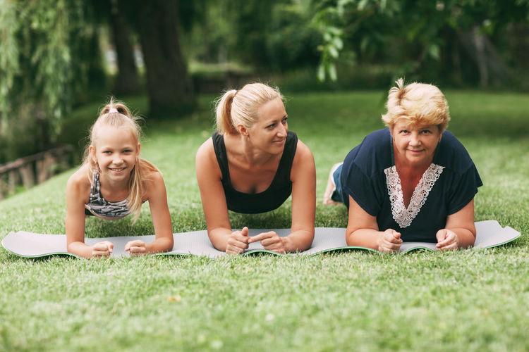 Multi generational family exercising plank on grass
