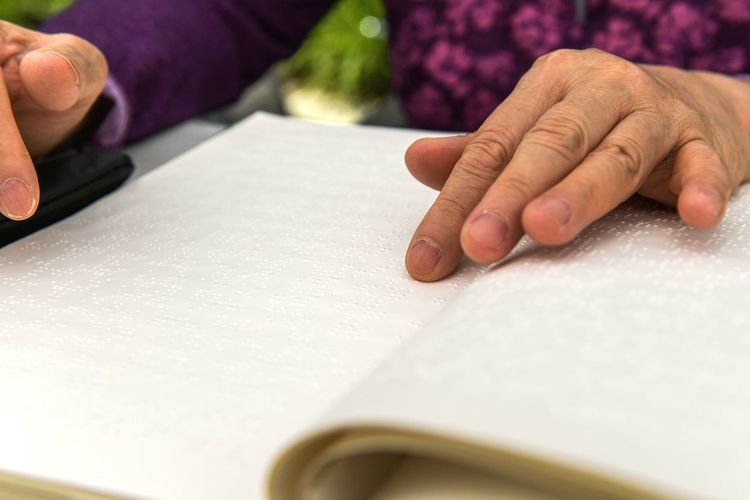 Hands of a blind person reading braille