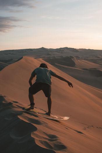 Rear view of man sandboarding at desert