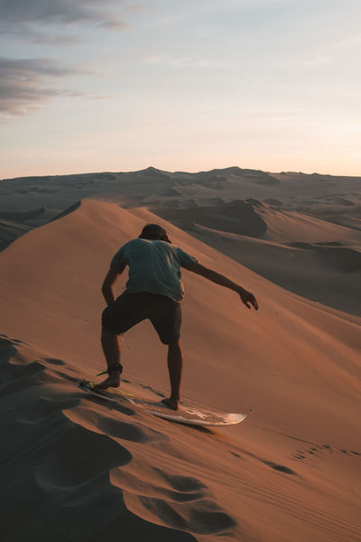 Sunset sandboarding rides down the dunes of Huacachina. Sky Tranquil Scene Land Nature Outdoors Desert Sand Sand Dune Arid Climate South America Latin America Explore Discover  Sunset Real People Lifestyles Non-urban Scene Rear View Men One Person Sport Casual Clothing Leisure Activity Surf Balance