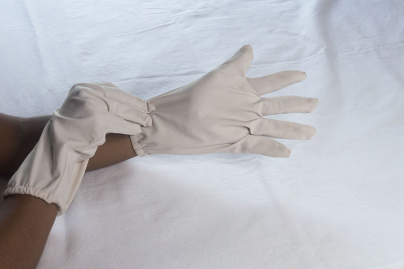 Close-up of hands on bed