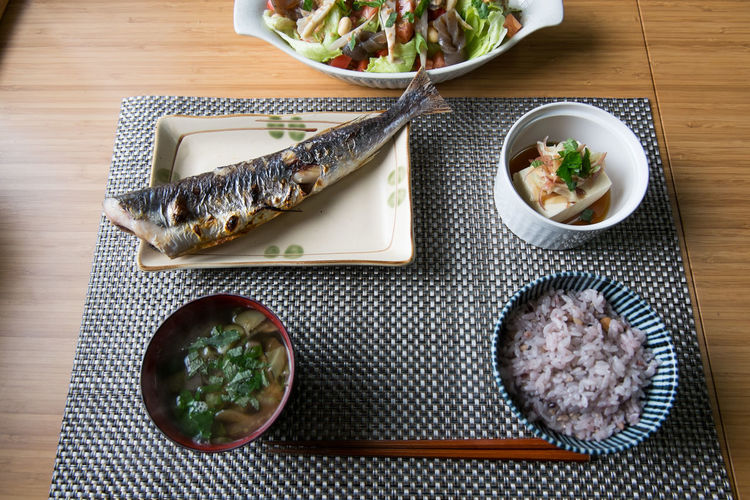 High angle view of fish in plate with rice and soup on table