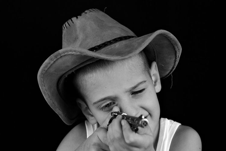 Close-up of boy wearing hat holding toy gun against black background