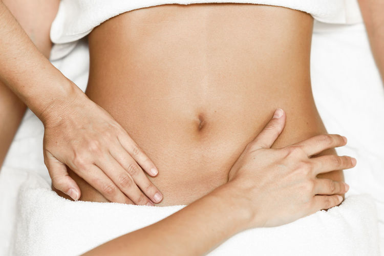 Midsection of therapist massaging woman in beauty spa