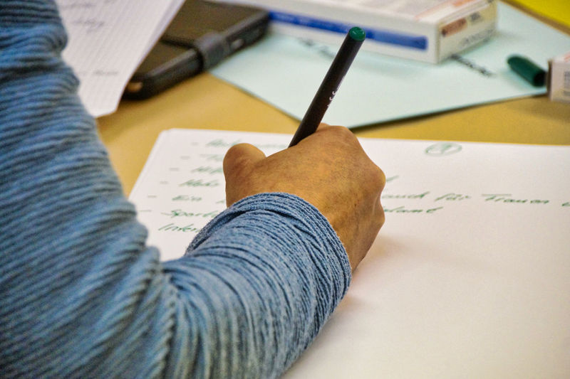 Cropped hand of man writing in paper on table