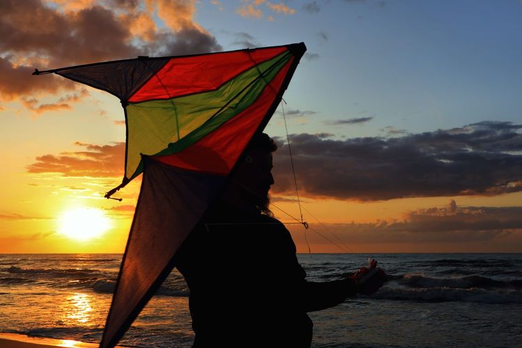 Silhouette of man holding kite while standing on beach