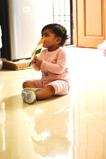 Girl holding indian flag while sitting on floor at home