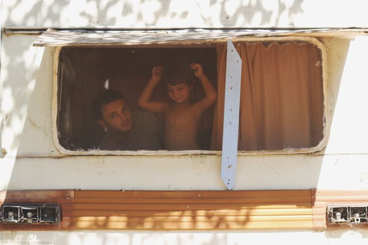 Portrait Of Father With Son Seen Through Motor Home Window