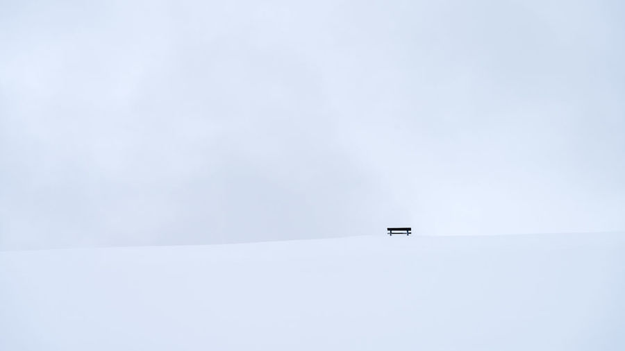 Empty lonely bench far away in white winter landscape Copy Space Day Tranquil Scene No People Beauty In Nature Mode Of Transportation Tranquility Scenics - Nature Nature Water Sparse Transportation White Color Nautical Vessel Winter Travel Distant Sky