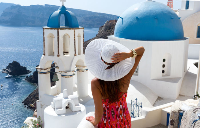 Woman with white hat enjoys the view from the Caldera in Santorini, Greece Architecture Behind Caldera Church Dome Dress Fashion Greece Hat Hat Leisure Activity Lifestyles Nature One Person Outdoors Rear View Santorini Sea Sky Standing Summer Travel Travel Destinations White Woman