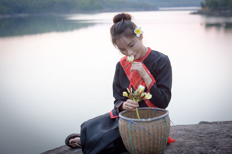 Close-up of woman in traditional clothing holding flowers at lake