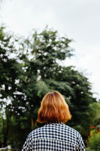 Rear view of woman against trees against sky