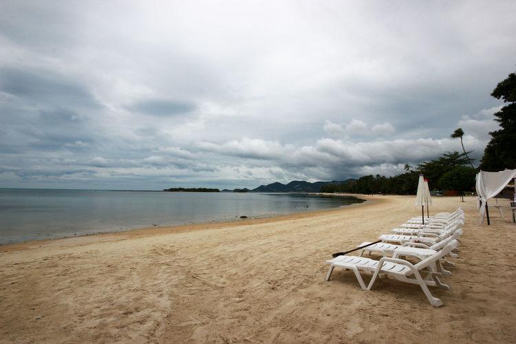 Empty chairs on beach against sky