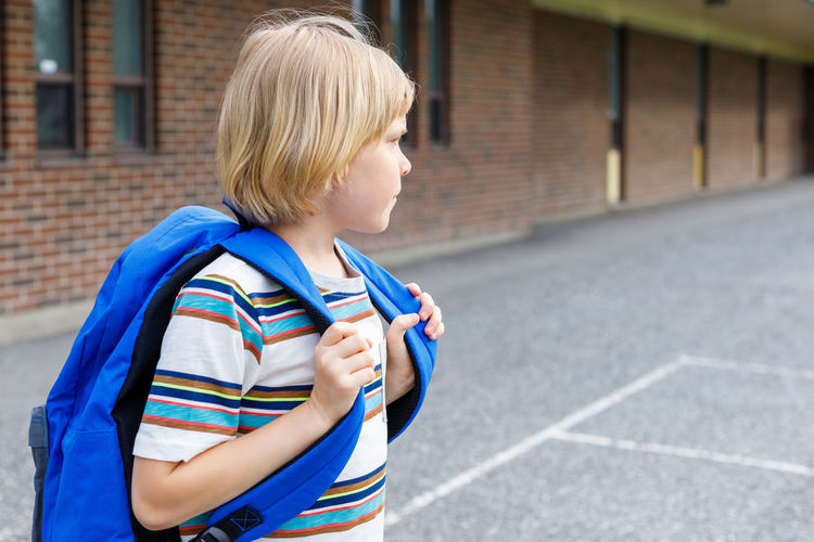 Beautiful child near school building at the schoolyard. little blond student with blue backpack.