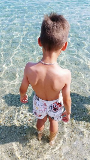 Rear view of shirtless boy standing in sea