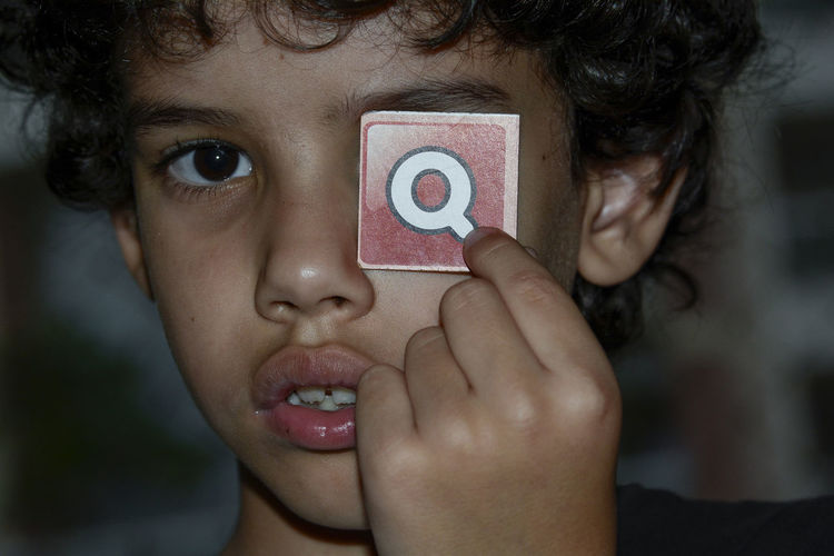 I asked my older boy when he was playing with his school letters what the letter Q would look like and he said my eye crying (eye with tears), and he did put the letter on his eye, and I took some pictures of what he did with it!!.... Childhood Crying Crying Child Portrait Q