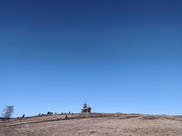 Panoramic view of land against clear blue sky