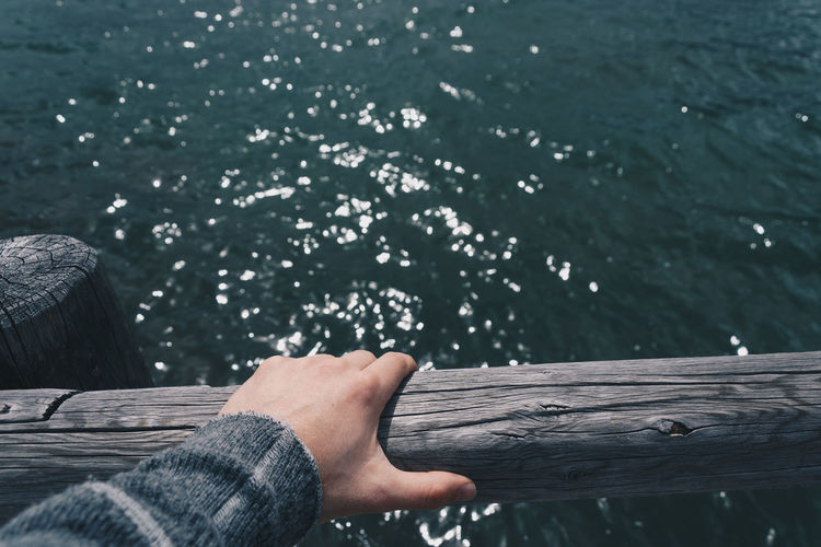 Cropped Hand Of Person On Wooden Railing Against Pyramid Lake At Jasper National Park