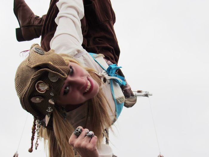 Portrait of happy woman wearing pirates costume hanging against clear sky