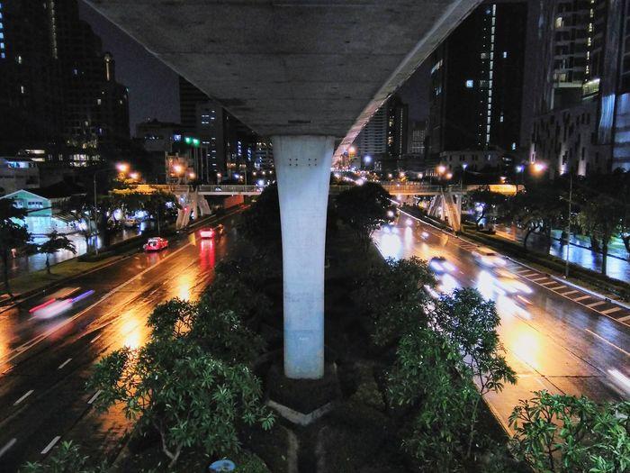 Bridge amidst illuminated city streets at night