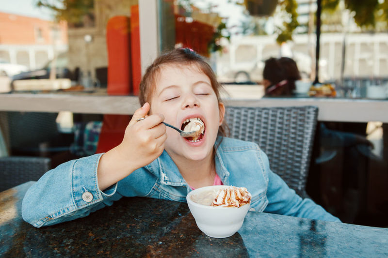 Close-up of girl eating ice cream at restaurant