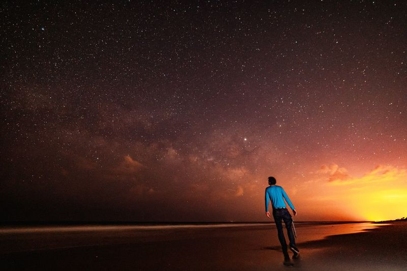 Rear view of man standing at beach against star field