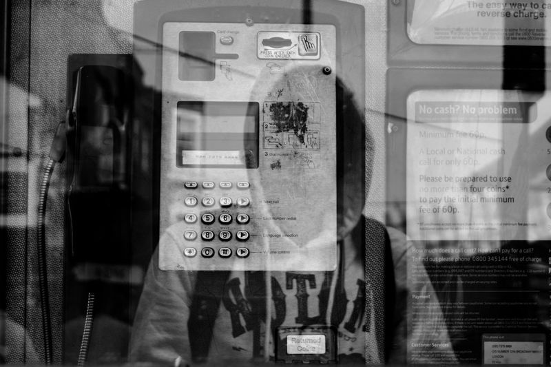 Telephone in booth seen through glass with reflection of person