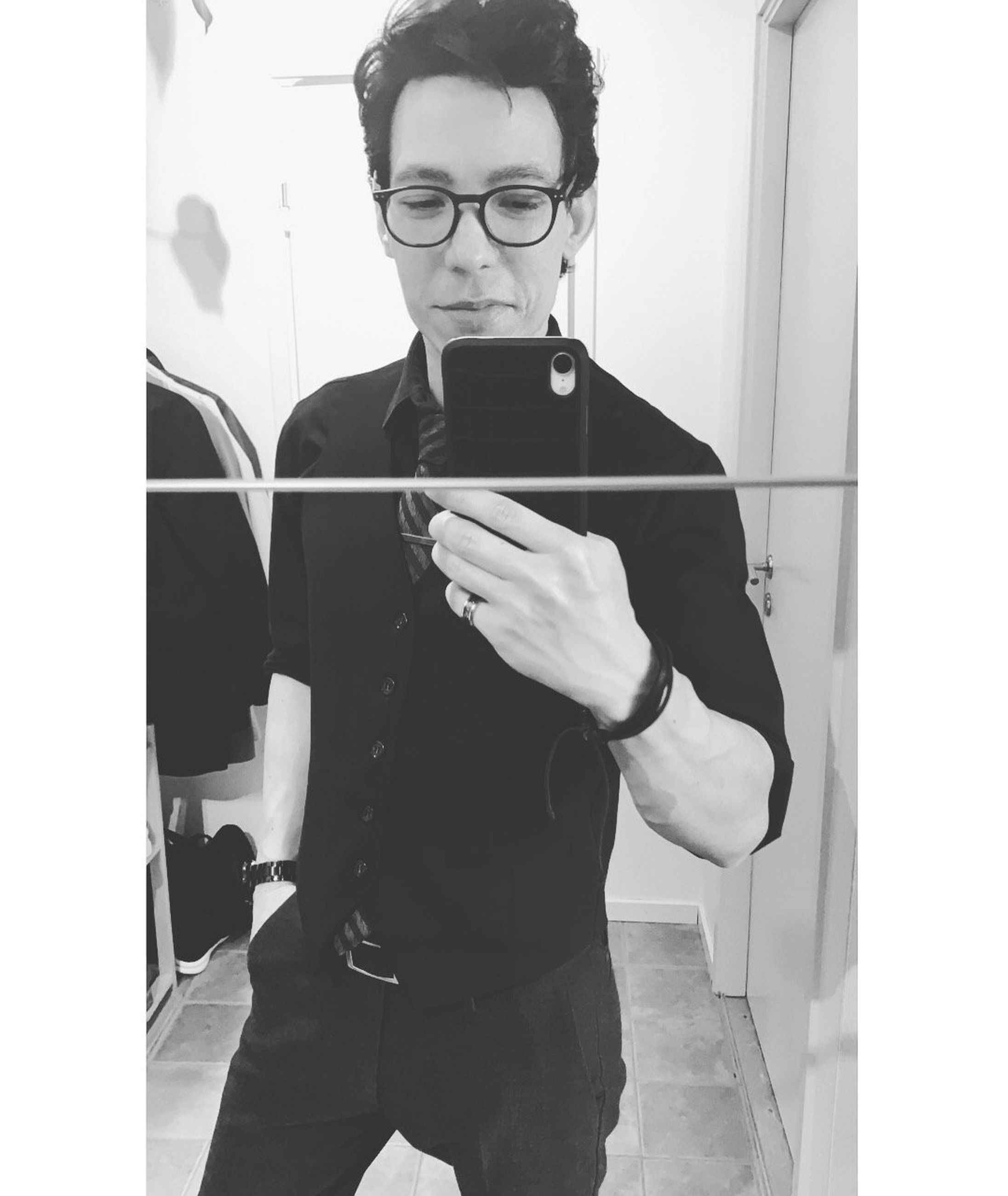 glasses, one person, eyeglasses, standing, real people, technology, wireless technology, holding, mobile phone, young men, front view, young adult, casual clothing, communication, smart phone, indoors, lifestyles, three quarter length, mirror