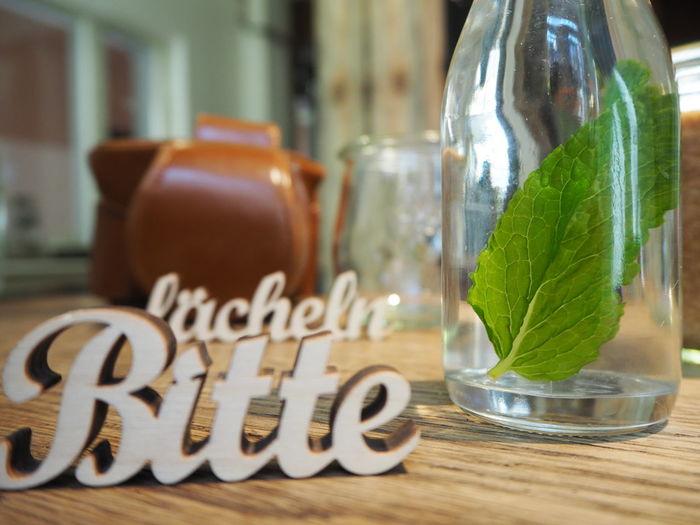 Bitte lächeln sign in Cologne in a cafe. Cafe Cologne , Köln,  Decoration Design Drink Glasbottle Healthy Lifestyle In A Cafe Mint Please Smile Table Water Wood